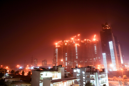 Under construction skyscraper shot at night in gurgaon Stock Photo