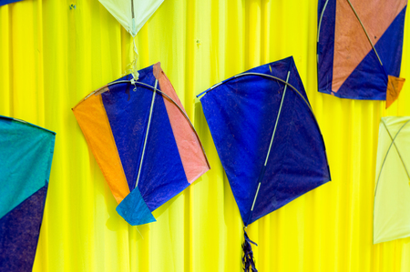 Indian handmade kites mounted on a fabric wall for decor Stock Photo