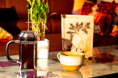French press filled with coffee, cup, bag of grounds shot in golden light Imagens
