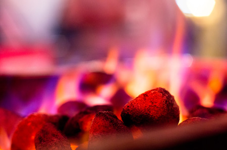 Flaming coals hot rocks with multicolored flames for barbeque