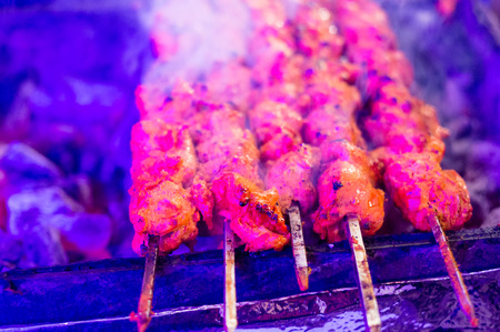Paneer and meat tikka roasting on skewers under colored light