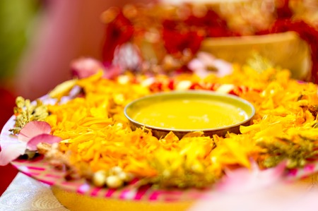 Traditional Haldi turmeric kept on a flower plate for the hindu marriage ceremony