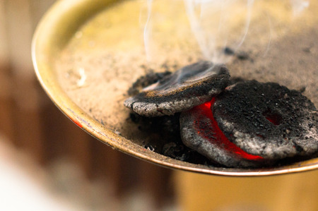burning dung cake coal embers taken from the holika dahan fire hindu festival of holi Stock Photo