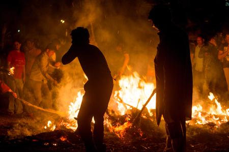 Silhouette of people in front of fire roasting grain for Holi Lohri festival
