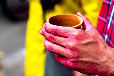 Colorful hands holding earthenware cups of thandai on hindu festival holi