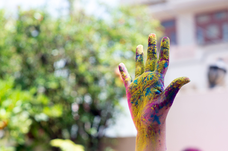 Colorful hand shot against a blurred background during the hindu festival of Holi 스톡 콘텐츠
