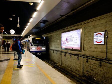 Motion blur of metro train arriving at a metro station while people watch