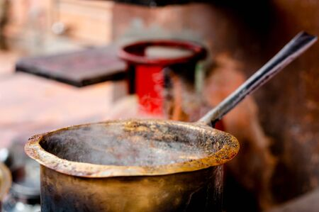 Tea boiling in a dirty open saucepan on a roadside stall in indian city. Tea vendors or thadis are common all over the country in markets and in travel stops. The cosntalntly boiling tea is tasty and refreshing