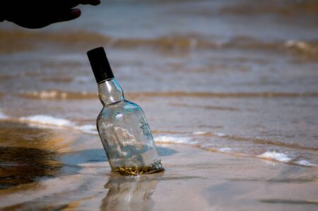 Upturned glass bottle buried in the sand with waves, surf and sand in the background at Diu beach Gujarat India. Shows the place where most of gujarat comes to consume alcohol given gujarat is a dry state. Can show the thrash on the beach or a party in progress