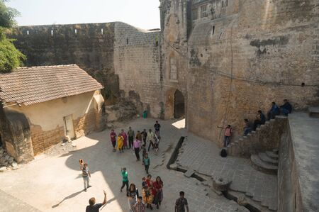 Diu, Gujarat, India - Circa 2018: Families and people entering the famous landmark fort diu through the main gate in gujarat. Shows the amazing stone arch gate and buildings around this famous tourist attraction. A must visit place to travel to and discov Editorial