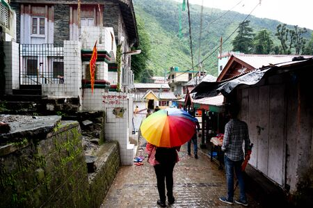 Young indian girl with a colorful umbrella in a busy market place street in McLeodganj