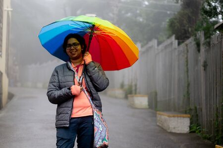 Young indian girl with a colorful umbrella standing on a foggy street in himachal pradesh Stock Photo