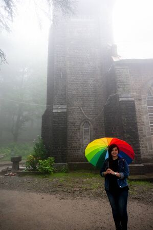 Young indian girl standing in front of a foggy st john of wilderness church a famous public monument