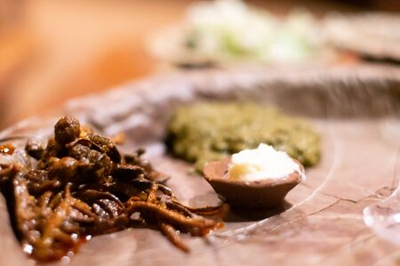 Rajasthani exotic dish of Ker Sangri with a small earthenware pot of white butter shot with shallow depth of feild
