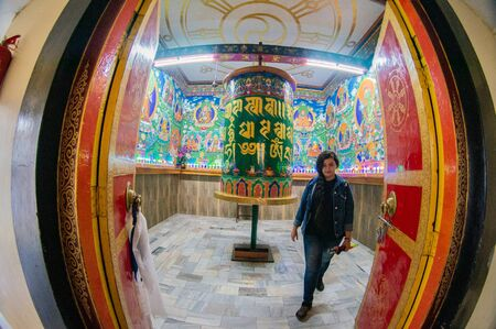 Beautiful huge bhuddhist prayer wheel in an ornately decorated room shot with a fisheye lens Stock fotó