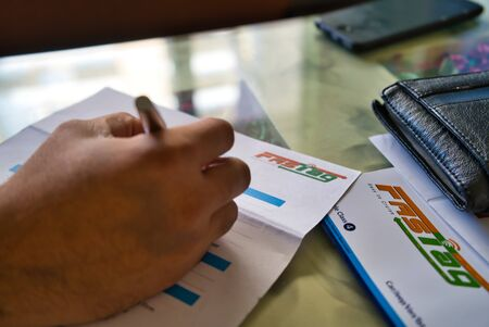 Gurgaon - India, Circa 2019: Photograph of Fast Tag application form being filled with a fountain pen, along with a wallet and a mobile phone on a beautifully decorated table. Fast tag is expected to make toll stops cash and hassle free and was implemente Redakční