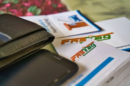 Gurgaon - India, Circa 2019: Photograph of Fast Tag with other application forms with a pen for fast tag, fastag, wallet and a mobile phone on a beautifully decorated table. Fast tag is expected to make toll stops cash and hassle free and was implemented