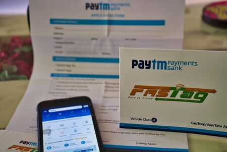 Gurgaon - India, Circa 2019: Photograph of Fast Tag on a beautifully crafted table along with a mobile phone on the table, the application form provided by PayTM payment bank. Fast tag is expected to make toll stops cash and hassle free and was implemente