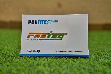 Gurgaon - India, Circa 2019: Photograph of Fast Tag provided by PayTM Payment Bank on green grass Fast tag is expected to make toll stops cash and hassle free and was implemented on 15th December 2019