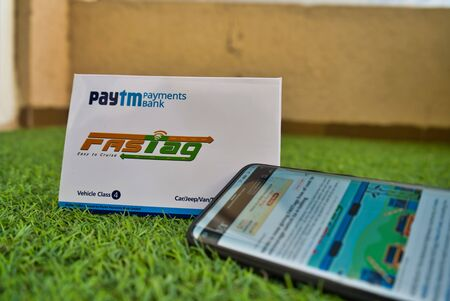 Gurgaon - India, Circa 2019: Photograph of Fast Tag provided by PayTM Payment Bank on green grass with a mobile phone logged into fast tag website. Fast tag is expected to make toll stops cash and hassle free and was implemented on 15th December 2019