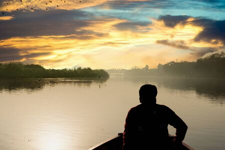 silhouette of boatsman rowing out into the yamuna ganga river in the morning 免版税图像