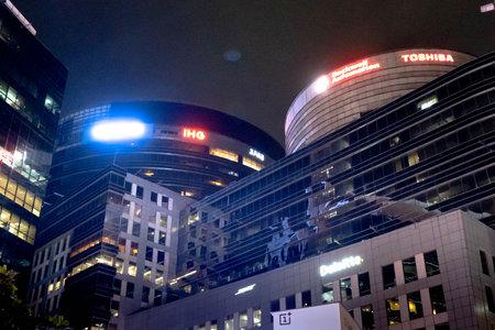 Night shot of huge skyscraper glass buildings with lit windows, lights and brand names in cyberhub gurgaon