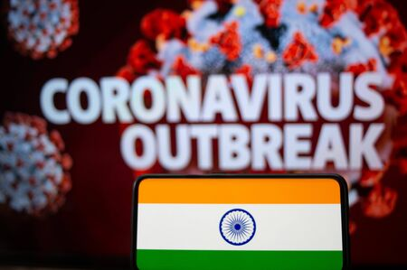 Photograph of the Indian Flag open on a mobile phone in front of a screen with the words Coronavirus outbreak mentioned on it. 版權商用圖片