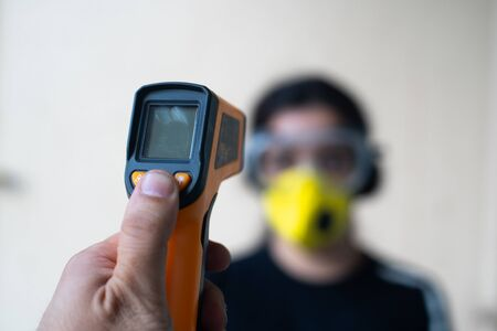 Infrared non contact thermometer being used to check an out of focus young indian girl wearing goggles and a mask during the current coronavirus pandemic while the city recovers from lockdown and slowly goes back to work