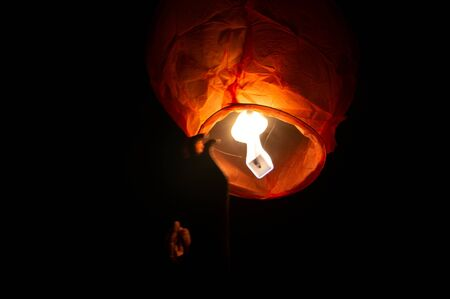 A red coloured sky lantern with the flames showing clearly lifiting off