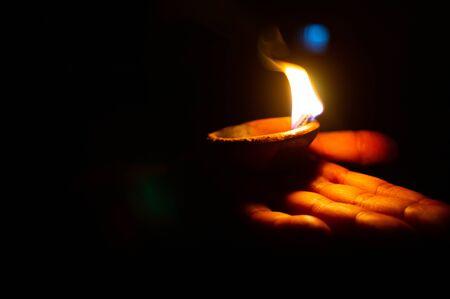 Beleuchtete Diya- oder Tonlampe auf der Handfläche einer Person Standard-Bild