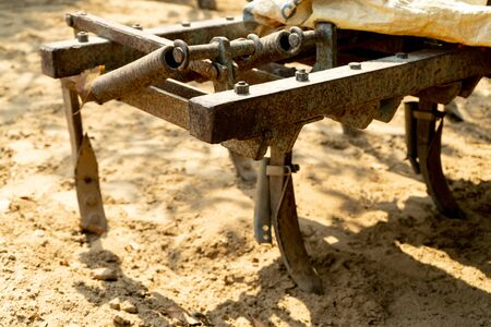 Close up of rusted plough on the back of a tractor digging into mud for crop planting . Shows how agriculture in india is fast modernizing with new tools and equipment to feed the ever increasing population