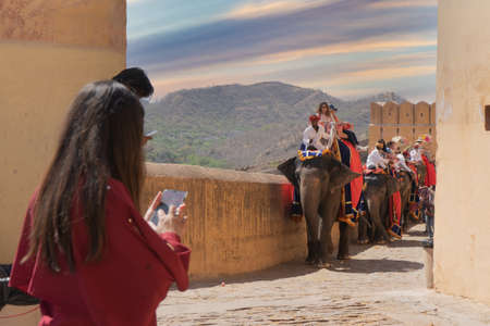 Jaipur, India - circa 2020 : people watching elephants, with tourists seated on it's back, entering the gates of the amber fort while it sprays itself with water to cool down on the hot day. The high stone walls, slippery stone path deters armies and hors