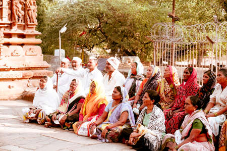 Indore, madhya pradesh, India - circa 2020 : Vintage village scene with older men and women from an indian village sitting cross legged on the ground in saree and kurta pyjama. Shows the closeness, happiness and fun that indian communities enjoy together