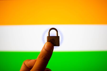Photographs of the indian flag with orange, white and green colours with a hand holding a lock in front of it to symbolize the lockdown in the country