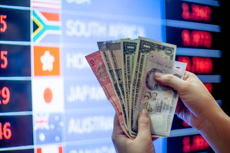 Hands holding multiple currency notes like american dollar, malaysian ringgit, singapore dollar, Indian rupee with backgound of a currency exchange forex chart