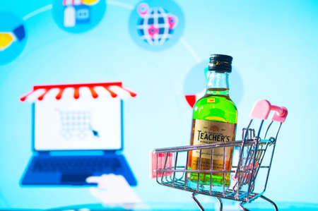 A bottle of whiskey in a trolley in front of a bright board
