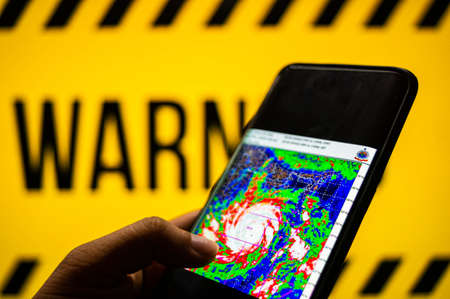 Mobile phone logged into photo of cyclone with warning background Sajtókép