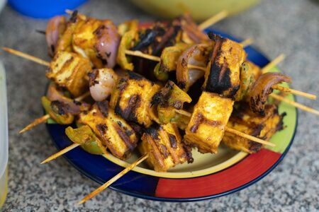 shot of home made grilled tandoori paneer charred with shimla mirch pepper onion tomatoes served with green chutney sauce a popular snack in north India