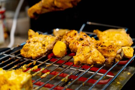 chicken grilling over a hot electric grill with hot rods at home barbeque