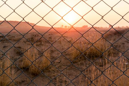 Chain link fence blocking the passage to beautiful sunset with barren desert with bushes and mountains in the distance