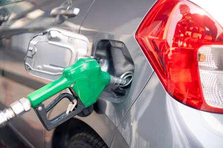 Man at a petrol pump fuel station inserting nozzle into fuel tank of a car and starting the fuel pumping in the auto cut off petro diesel pump