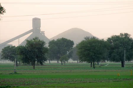 Panning shot of green natural feild with large trees fading off into the foggy distance and the silhouette of a factory in the distance showing the mixing of rural agricultural lift and manufacturing in smaller indian towns and villages