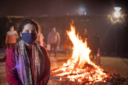 Young indian girl wearing a mask in front of a large wood fire on the indian festival of lohri holly celebrating