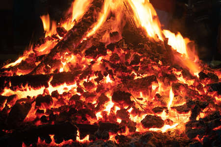 Close up macro shot of wood fire with log embers and flames coming out shot during the indian festival of holi lohri or Guy fawkes day