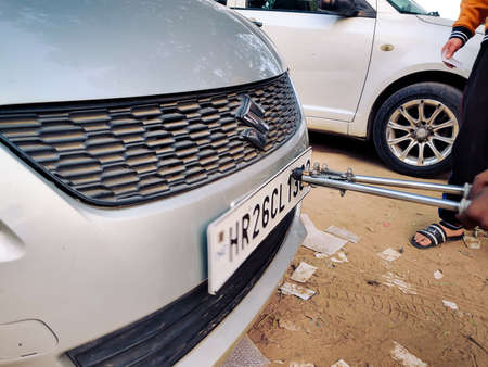 Man using a riveting locking tool to affix a tamper proof HSRP high security registeration plate to a maruti swift car at a registeration center