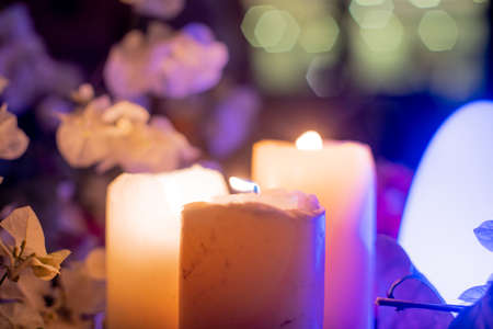 zoomed in shot of large thick wax candles with flames lit and colorful flowers all round and led lights flickering showing the table decorations at a valentine , wedding , engagement dinner at night with an intimate beautiful display