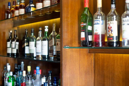 Soft focus shot of wooden shelf in a bar pub hotel filled with liqor bottles from top brands of whiskey, gin, rum, vodka and more