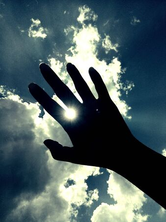 hope: Sunlight shine through the space between fingers. Stock Photo