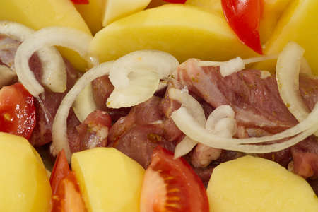 pork meat, potatoes, tomatoes and onions, ready to bake