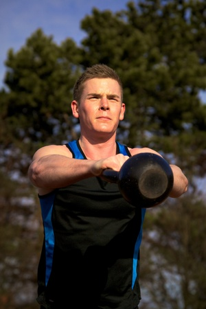 kettles: Young man doing kettlebell exercise outside in park Stock Photo